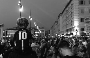 Black and white image of behind a crowd of sports fans lining the streets in France.
