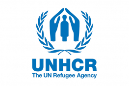 The UNHCR logo - a blue pair of hands shelters a cartoon person, surrounded by a wreath, underneath which there is the blue text 'The UN Refugee Agency'.