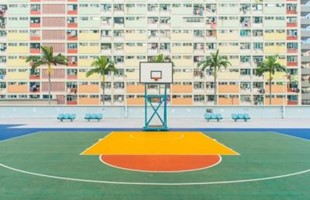 Empty basketball court in front of block of apartments.