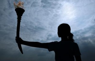 Silhouette of a female holding the olympic torch.