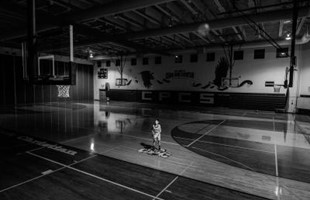 Black and white image of basketball player alone on a basketball court indoors.