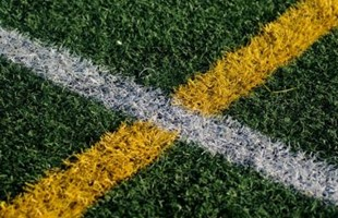 Close up image of painted lines on grass sports pitch.